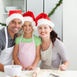 Portrait of a man with wife and daughter cooking Christmas biscu - Stock Photo