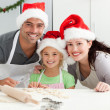 Cheerful family kneading biscuits for Christmas — Stock Photo