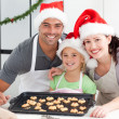 Happy woman with husband and daughter ith their biscuits ready — Stock Photo