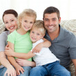 Adorable family sitting on the sofa and smiling — Stockfoto