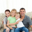 Joyful family sitting on the sofa — Stock fotografie