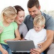 Adorable family working together on a laptop sitting on the sofa — Stock Photo
