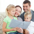 Adorable family reading a book together in the living-room — Stock Photo