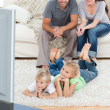 Adorable siblings watching television with their parents lying o - Stock Photo