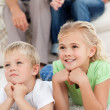 Stock Photo: Brother and sister watching television on floor with their p