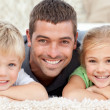Children and father looking at the camera on the floor — Stockfoto