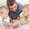 Children and father looking at a book on the floor — Stock Photo