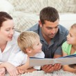 Family looking at a book on the floor — Stock Photo #10838604