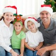 Portrait of a happy family with Christmas hats sitting on the so — Stockfoto