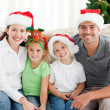 Portrait of a happy family with Christmas hats sitting on the so — Foto Stock