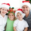 Happy family with christmas hats sitting on the sofa — Stok fotoğraf
