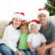 Adorable family at Christmas sitting in the living-room — ストック写真