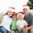 Adorable family at Christmas sitting in the living-room — Stok fotoğraf