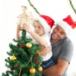 Happy father helping his son to put an angel on the Christmas tr - Foto de Stock