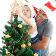 Foto Stock: Father and son decorating their christmas tree