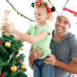 Stock Photo: Happy father helping his daughter to put an angel on the Christm
