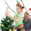 Foto Stock: Cute little girl decorating the christmas tree with her father