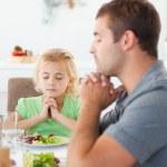 geconcentreerde vader en dochter bidden voor het eten van hun sal — Stockfoto