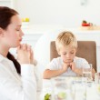 Concentrated little boy praying with his mother before eating th — Stock Photo