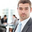 Charismatic businessman standing in the foreground — Stock Photo
