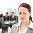 Charismatic businesswoman standing in the foreground while her t — Stock Photo