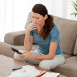 Anxious woman calculating her debts sitting in the living-room — Stock Photo