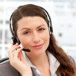 Stock Photo: Pretty businesswomwith earpiece and looking at camera
