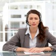 Royalty-Free Stock Photo: Attractive businesswoman speaking using headset sitting at a tab