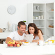 Happy couple reading the newspaper in the kitchen — Stock Photo