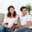 Lovely couple drinking red wine sitting on the sofa — Stock Photo