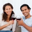 Portrait of a couple clinking glasses of red wine on the sofa — Stock fotografie