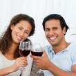 Happy couple drinking red wine sitting on the sofa — Stock Photo