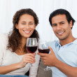 Happy couple clinking glasses of red wine on the sofa — Stok fotoğraf