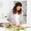 Pretty woman cutting vegetables while preparing a salad — Stock Photo #10839206
