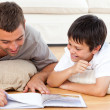 Happy father and son reading a book together on the floor — Stock Photo