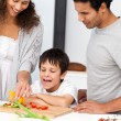 Happy family preparing a salad together in the kitchen — Stock Photo