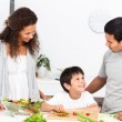 Happy family cutting vegetables together in the kitchen — Stockfoto