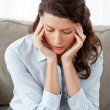 Pretty businesswomhaving headache sitting on sofa — Stock Photo #10839496