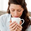 Pretty businesswoman smelling her coffee sitting on the sofa - Stok fotoğraf