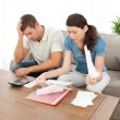 Worried couple looking at their bills in living room — Stock Photo #10839668
