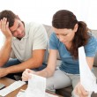 Stressed man and woman looking at their bills in the living room — Stock Photo
