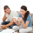 Stock Photo: Stressed couple doing their accounts sitting on sofa
