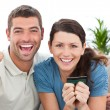 Portrait of a happy couple holding their credit card on the sofa — Stock Photo