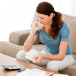 Stressed woman calculating her bills sitting on the sofa — Stock Photo #10839716