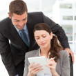 Happy businessman helping a businesswoman working at her desk — Foto de Stock