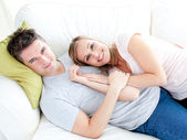 Caress young couple lyingo together on the sofa — 图库照片