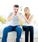 Shocked man sitting on the sofa with his girlfriend — Stock Photo