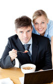 Enamored couple of businesspeople smiling at camera eating cerea — Stock Photo