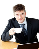Charming young businessman holding a cup smiling at the camera — Stock Photo