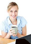 Glowing businesswoman drinking coffee smilng at the camera — Stock Photo